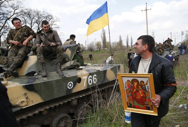 A local resident holding an Orthodox icon talks with soldiers of Ukrainian Army, as they are blocked by people on their way to the town of Kramatorsk on Wednesday, April 16, 2014. (Photo by Sergei Grits/AP Photo)