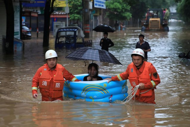Rescue workers wade through flood waters as they evacuate a woman with an inflatable swimming pool on a street following heavy rainfall in Pingxiang, Jiangxi province, China on July 10, 2019. (Photo by Reuters/China Stringer Network)