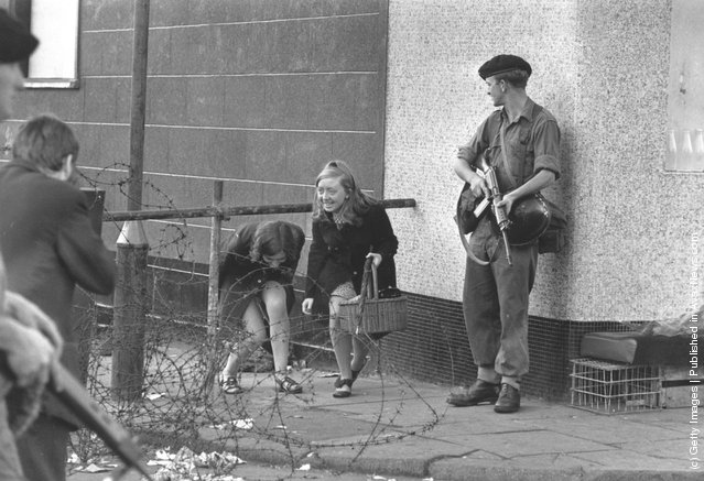 1969:  Two young women climbing under a barricade next to an armed soldier on the Falls Road, Belfast