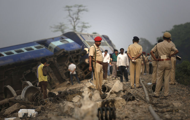 Indian policemen stand by a train that derailed near Jagiroad Railway Station, about 90 kilometers (56 miles) east of Gauhati, India, Wednesday, April 16, 2014. According to a Northeast Frontier Railway officer, dozens of people were injured when the train jumped the tracks and derailed early Wednesday. (Photo by Anupam Nath/AP Photo)