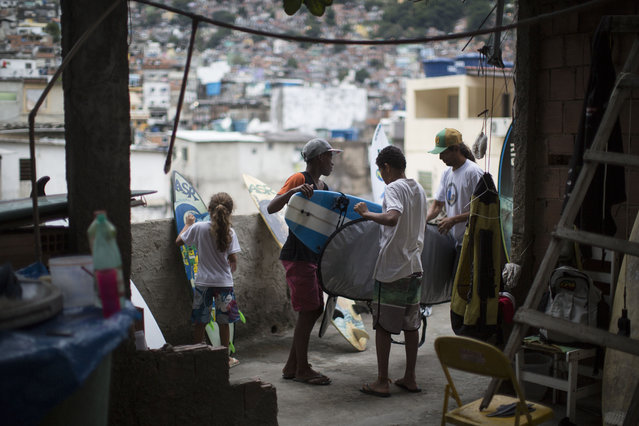 Marcio Pereira da Silva, right, founder of the Rocinha Surf Association, ASR, is helped by young surfers as they store boards at their headquarters at Rocinha slum in Rio de Janeiro, Brazil, Thursday, July 2, 2015. ASR has given free lessons to over 2,000 children from Rio's shantytowns in the hopes of keeping the boys, who are mostly in their early teens and a few girls occupied by the sport and off the streets. (Photo by Felipe Dana/AP Photo)