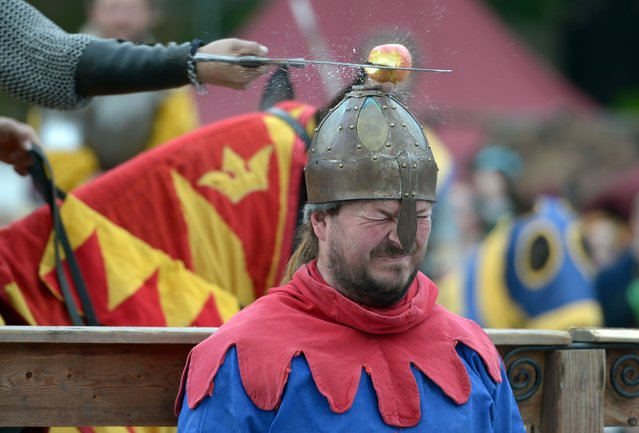 A man smashes an apple with a sword placed on the head of a man wearing a knave costume during the Easter knight event on April 21, 2014 in Berlin. The easter knight event delivers an insight into medieval lifestyle. (Photo by Rainer Jensen/AFP Photo/DPA)