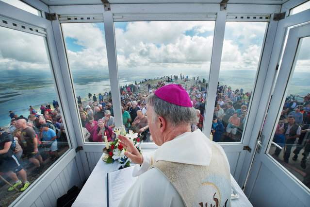 """Mass on the Summit of Irelands Holy Mountain"". ArchBishop Of Tuam Michael Neary celebrates mass with Pilgrims on the summit of Croagh Patrick during the Annual pilgrimage in honour of Saint Patrick, Ireland's patron saint. Croagh Patrick overlooks Clew Bay in County Mayo, which overlooks Clew Bay in County Mayo, Ireland and is considered the holiest mountain in Ireland. Photo location: Croagh Patrick, County Mayo, which overlooks Clew Bay, Ireland. (Photo and caption by Michael Laughlin/National Geographic Photo Contest)"