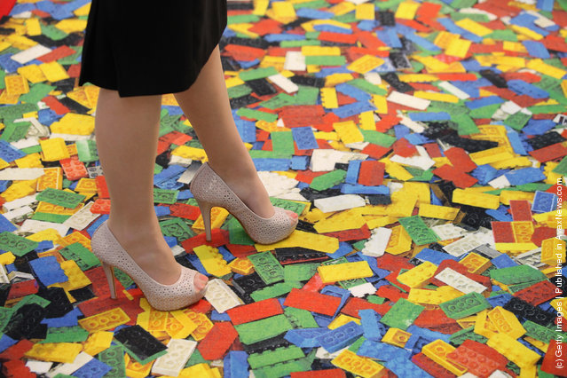 A woman stands on a carpet with a Lego brick design at the 2012 London Toy Fair