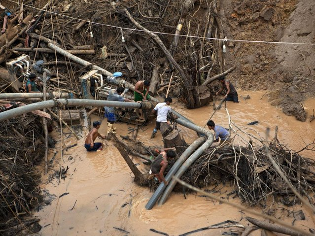 """Miners known as """"Maraqueros"""" ready a rustic type of hydraulic jet known locally as a """"Chupadera"""", after hauling the device about 16-meters deep into a crater at a gold mine process in La Pampa in Peru's Madre de Dios region. A new threat now looms for the estimated 20,000 wildcat miners who toil in huge scar of denuded rainforest known as La Pampa. (Photo by Rodrigo Abd/AP Photo)"""