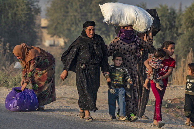 Civilians flee during Turkish bombardment on Syria's northeastern town of Ras al-Ain in the Hasakeh province along the Turkish border on October 9, 2019. Turkey launched a broad assault on Kurdish-controlled areas in northeastern Syria today, with intensive bombardment paving the way for an invasion made possible by the withdrawal of US troops. (Photo by Delil Souleiman/AFP Photo)
