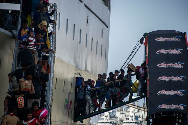 Passengers disembark from a ship on arrival at Surabaya port in eastern Java island on July 16, 2015 as Indonesians embark on a mass exodus to their hometowns to celebrate Eid al-Fitr marking the end of the holy fasting month of Ramadan. Cities in the world's most populous Muslim-majority country empty every year at the end of the holy month of Ramadan as people head to villages to celebrate Eid with their families. (Photo by Juni Kriswanto/AFP Photo)