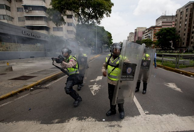 Bolivarian National police fire rubber bullets at anti-government demonstrators trying to march to the headquarters of the national electoral body, CNE, in Caracas, Venezuela, Wednesday, May 18, 2016. (Photo by Fernando Llano/AP Photo)
