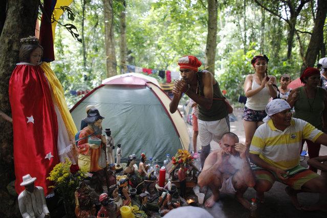 In this photo taken October 12, 2019, followers of indigenous goddess Maria Lionza smoke cigars during purification rituals and to deflect evil spirits, next to an altar featuring her statue, left, on Sorte Mountain where followers of the goddess gather annually in Venezuela's Yaracuy state. Many camped in tents among the old-growth forest while dedicating several days to spiritual ceremonies. (Photo by Ariana Cubillos/AP Photo)