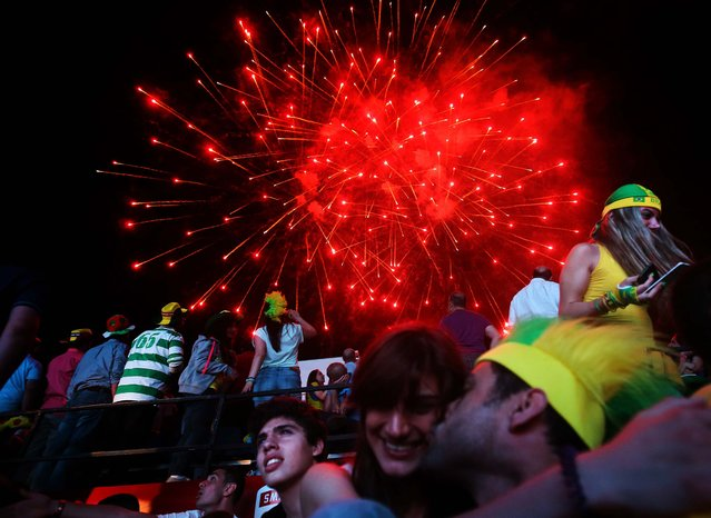 Fireworks light the sky over soccer fans who gathered to watch the match between Brazil and Croatia, in downtown Beirut, Lebanon. (Photo by Hussein Malla/Associated Press)