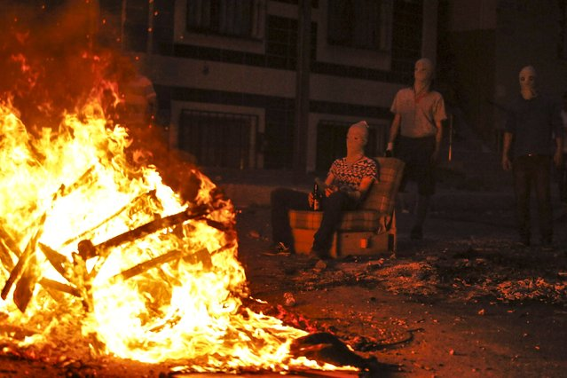 A far left-wing protester sits next to a burning barricade during a pause in clashes with riot police at a demonstration against the death of Gunay Ozarslan, a member of the far left People's Front who, according to local media reports, was killed by Turkish police during a security operation on Friday, in Istanbul's Gazi neighborhood, Turkey, July 26, 2015. (Photo by Huseyin Aldemir/Reuters)
