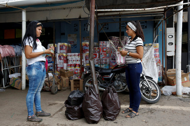 Women holding Venezuelan bolivar notes talk in front of a store that sells food and staple items in Puerto Santander, Colombia, June 3, 2016. (Photo by Carlos Garcia Rawlins/Reuters)