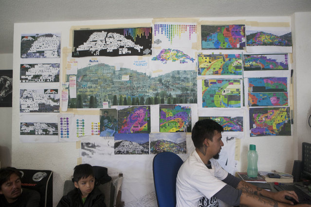 Blueprints and photos are displayed in the headquarters of the artist collective German Crew in Pachuca, Mexico, Thursday, July 30, 2015. German Crew has been working for a year and two months to create what they claim is Mexico's largest mural. The creative collective has used 20,000 liters of paint on 209 houses. (Photo by Sofia Jaramillo/AP Photo)
