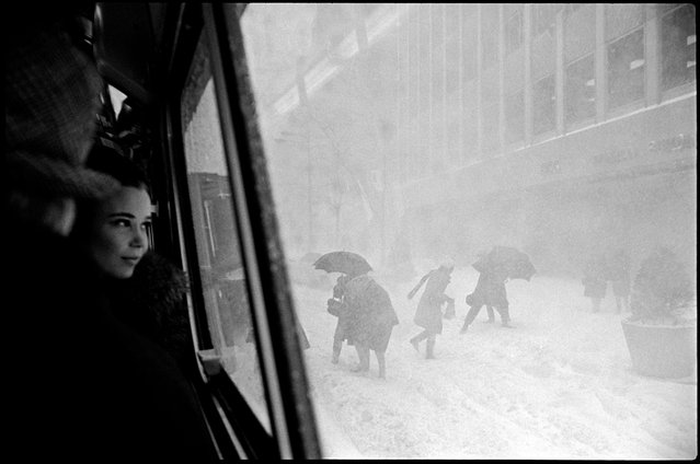 "New York City, USA, 1967. Girl in bus and figures in street during snowstorm. Ruth, Erich Hartmann's widow, writes: ""Perhaps this picture should be described not as a 'decisive moment', but as a 'unique moment' ... It is unlikely that ever again on a winter's day in New York would that same young woman be sitting in a bus near enough to where Erich was standing for him to take a picture of her that also included within the frame a well-spaced group of passengers outside struggling against the storm, some entering the bus from the snow-filled street, others leaving to face the wind and the cold"". (Photo by Erich Hartmann/Magnum Photos)"