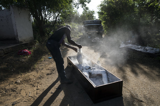 "Cemetery worker Roberto Jesus Sangroni, known by his friends as ""Makuka"", covers the body of Nerio Jesus Garcia with lime, moments after his autopsy to help reduce the smell, two days after his death as he prepares the body for a wake burial at the municipal cemetery in Cabimas, Venezuela, November 30, 2019. Garcia's mother found his corpse with a gun shot between his eyes on the bank of Maracaibo Lake following a phone call from a prisoner that her son had escaped from jail. (Photo by Rodrigo Abd/AP Photo)"