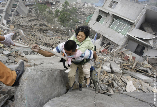 A rescue worker carries a survivor from a collapsed building in the old city district near a mountain at the earthquake-hit Beichuan county, Sichuan province, May 15, 2008