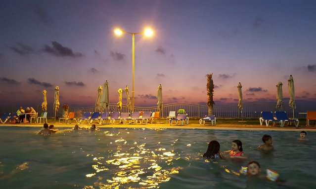 Palestinian children swim in a pool as they enjoy the warm weather with their families at the Blue Beach Resort in Gaza July 25, 2015. A luxurious new tourist resort has opened in the Gaza Strip, its manicured lawns, sparkling pool and private beach in stark contrast to the impoverished territory still struggling to recover from last year's war. (Photo by Ahmed Jadallah/Reuters)