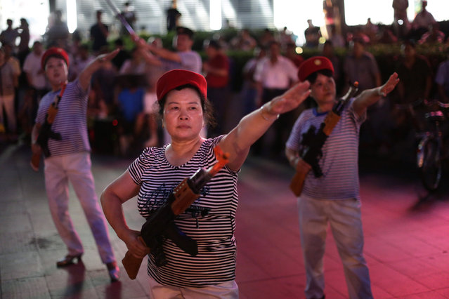"Chinese women holding toy guns dance to a revolutionary song as part of their daily exercise at a square outside a shopping mall in Beijing, June 29, 2014. About 30 local residents formed this ""Nanguan"" art group that enjoys performing and dancing to revolutionary songs as part of their nightly fitness activity. (Photo by Jason Lee/Reuters)"