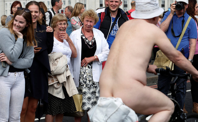 Women react as they watch cyclists participate in the World Naked Bike Ride, which organisers say is a protest against reliance on cars and oil, on Westminster Bridge London, Britain June 11, 2016. (Photo by Luke MacGregor/Reuters)