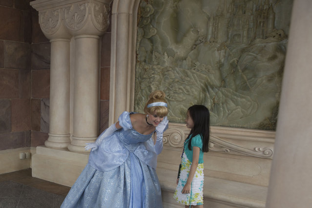 A woman dressed as a Disney character listens to a young Chinese girl during a tour on the eve of the opening of the Disney Resort in Shanghai, China, Wednesday, June 15, 2016. (Photo by Ng Han Guan/AP Photo)