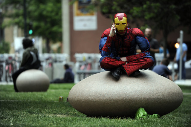 TJ Giannasca dressed as a hybrid of Spiderman and Iron Man talks on the phone as he takes a break during Denver Comic Con at the Colorado Convention Center in Denver, Colorado on June 14, 2014. (Photo by Seth McConnell/The Denver Post)