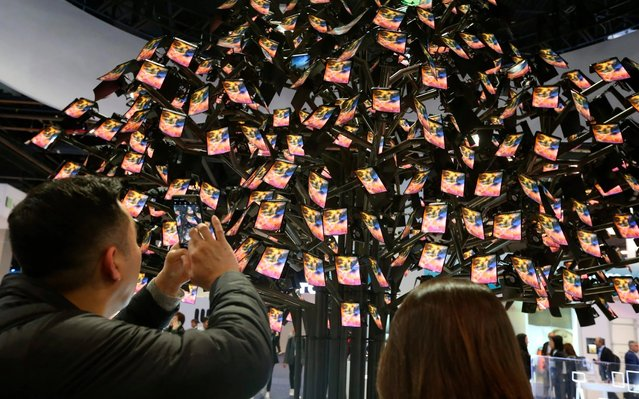 atrons take photos of Royole's fully flexible display and sensor technologies in an artistic tree decorated with some 1,000 screens of fully flexible displays during the CES tech show Wednesday, January 8, 2020, in Las Vegas. (Photo by Ross D. Franklin/AP Photo)