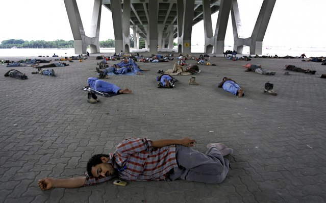 Construction workers sleep under an expressway bridge during their lunch break in Singapore, in this March 6, 2007 file photo. On August 9, 2015, Singapore will mark half a century of independence, and marvel at its leap from the third world to the first. But progress in the next few years will be less momentous. (Photo by Nicky Loh/Reuters)