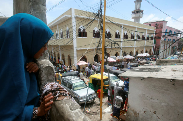 A Somali girl watches as the faithful attend prayers outside the Marwaas Mosque on the second Friday of the holy month of Ramadan in Mogadishu, Somalia June 17, 2016. (Photo by Ismail Taxta/Reuters)