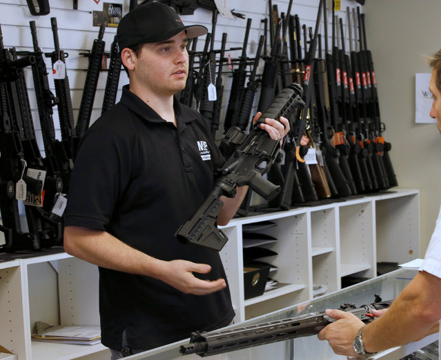 """Salesman Ryan Martinez shows a prospective buyer an AR-15 at the """"Ready Gunner"""" gun store in Provo, Utah, U.S., June 21, 2016. (Photo by George Frey/Reuters)"""