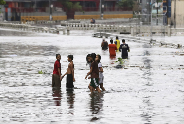 Residents wade along flooded roads as Typhoon Rammasun batters suburban Quezon city, north of Manila,  Philippines on Wednesday, July 16, 2014. Typhoon Rammasun knocked out power in many areas but it spared the Philippine capital, Manila, and densely-populated northern provinces from being directly battered Wednesday when its fierce wind shifted slightly away, officials said. (Photo by Aaron Favila/AP Photo)