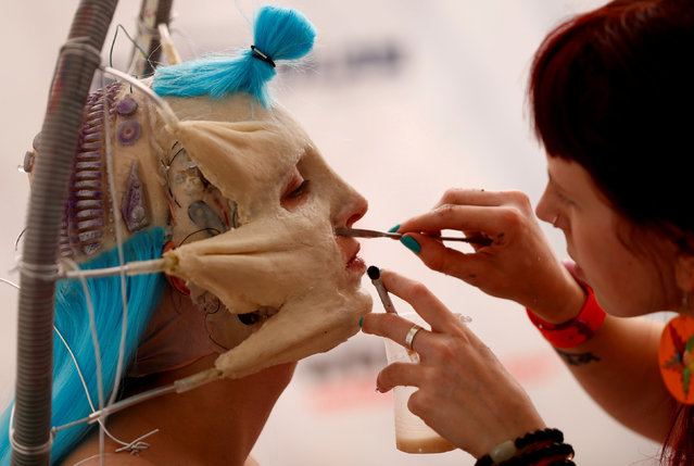 """An artist touches up makeup on a model during the """"World Bodypainting Festival 2017"""" in Klagenfurt, Austria July 28, 2017. (Photo by Leonhard Foeger/Reuters)"""