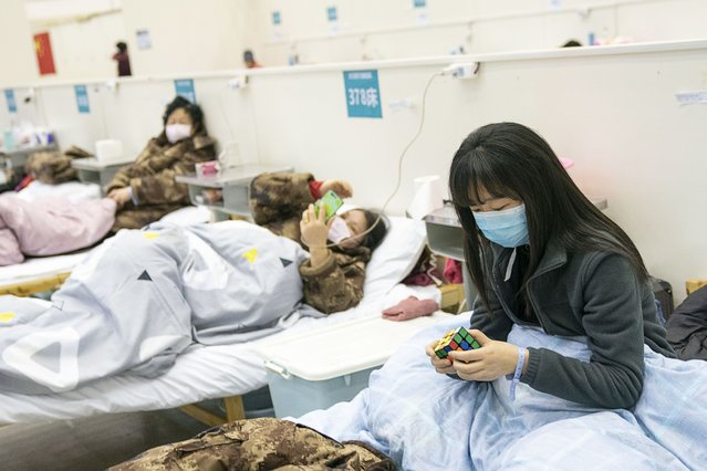 "A patient solves a rubik's cube at a temporary hospital converted from ""Wuhan Livingroom"" in central China's Hubei Province on February 10, 2020. In face of the outbreak of the novel coronavirus pneumonia epidemic, Wuhan authorities have transformed public venues such as exhibition centers and gymnasiums into temporary hospitals. The hospitals have a large capacity of treating patients with mild symptoms and play an important role in isolating the source of infection and cutting off the routes of infection during epidemic prevention. The first batch of patients was hospitalized on Feb. 5. (Photo by Chine Nouvelle/SIPA Press/Rex Features/Shutterstock)"