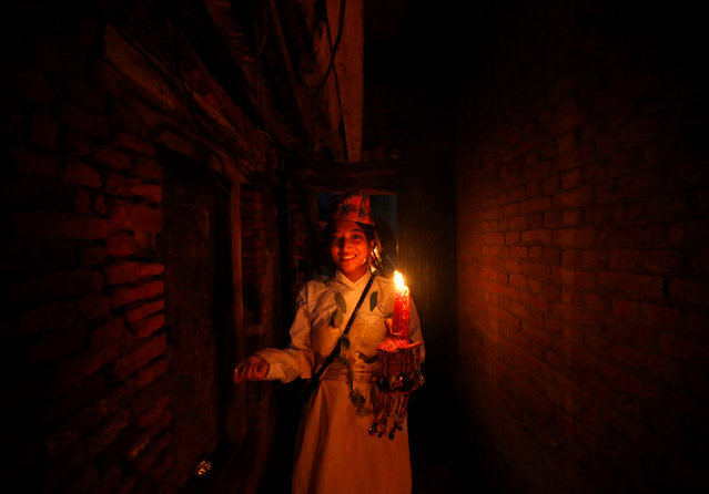 A devotee holding candle walks along the alley as she takes part in a parade commemorating the Neku Jatra-Mataya festival, the Festival of Lights, in Lalitpur, Nepal August 9, 2017. Devotees celebrate the Buddhist festival which marks the victory of Sakyamuni Buddha over Mara, by praying for the souls of departed family members and holding parades throughout the city. (Photo by Navesh Chitrakar/Reuters)