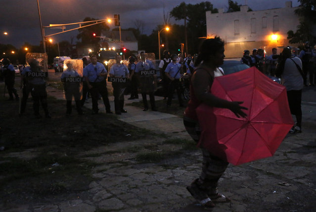 A lady crosses in front of the police line as they stand guard in riot gear where protesters gather on Walton Avenue and Page Boulevard on Wednesday, August 19, 2015, in St. Louis. (Photo by Laurie Skrivan/St. Louis Post-Dispatch via AP Photo)