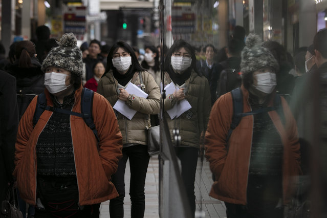 Commuters wearing protective face masks walk on a sidewalk Monday, January 27, 2020, in the Shinjuku district of Tokyo. China has extended its Lunar New Year holiday three more days to discourage people from traveling as it tries to contain the spread of a viral illness that has caused dozens of deaths. (Photo by Jae C. Hong/AP Photo)