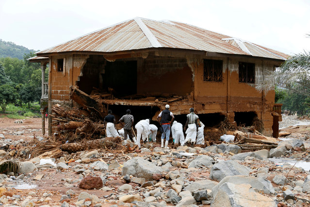 Rescue workers are seen searching through rubbles around a house for bodies at Pentagon, in Freetown, Sierra Leone August 18, 2017. (Photo by Afolabi Sotunde/Reuters)