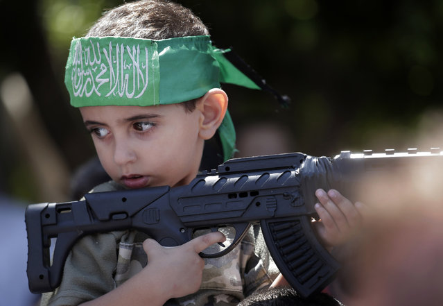 A Palestinian by holds a toy gun as he participates at a Hamas rally in Gaza City, Gaza Strip, Thursday, Aug. 7, 2014. Thursday's rally drew several thousand supporters and a senior Hamas official has told supporters at the rally that the war with Israel won't be over until the group's political demands are met. Israel and Hamas were holding indirect negotiations in Cairo, Egypt about new border arrangements for blockaded Gaza and extending a cease-fire. (Photo by Lefteris Pitarakis/AP Photo)