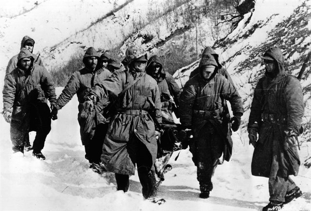 Marines carry a wounded comrade through snow to a cleared airstrip for evacuation during the Korean War, 1950. (Photo by Keystone)