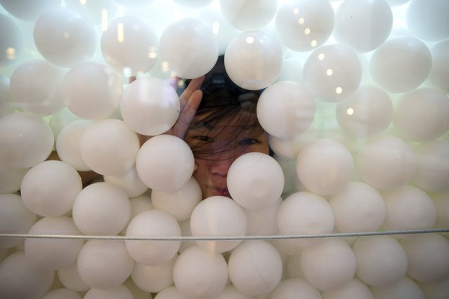 "A woman peers out through a glass wall of the ""JumpIn!"" ball pit, an interactive art installation by creative agency Pearlfisher made up of 81,000 white balls, in New York City August 25, 2015. The installation is hosted at the agency's new SoHo office and open to the public from August 21 till September 21, to promote how play can yield results for creative thinking. (Photo by Mike Segar/Reuters)"
