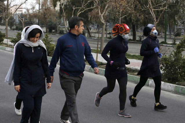 Two women jog with face masks on as others walk while enjoying their weekend afternoon at Pardisan Park in Tehran, Iran, Friday, February 28, 2020. Iranians in Tehran on Friday found time to enjoy their weekend, even as authorities canceled Friday prayers and closed universities, schools and parliament over fears about the new coronavirus. (Photo by Vahid Salemi/AP Photo)