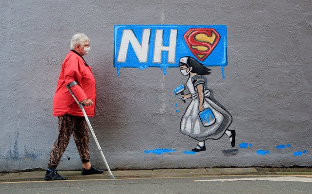A woman wearing a facemask walks past a mural supporting the NHS, by artist Rachel List, on the side of Horse Vaults pub in Pontefract, Yorkshire on April 3, 2020, as the UK continues in lockdown to help curb the spread of the coronavirus. (Photo by Danny Lawson/PA Images via Getty Images)