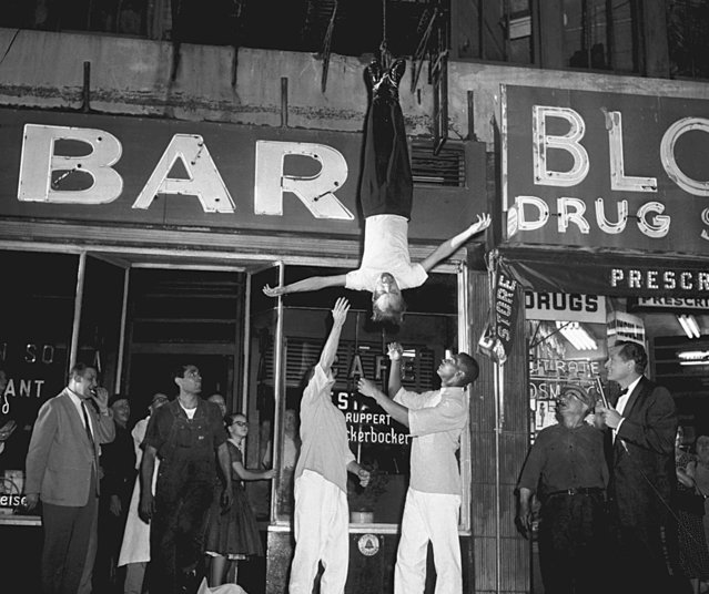 "Magician James Randi, an escape artist from Toronto, Canada, appears on the CBS-TV show ""It's Magic"", at 65th Street and Broadway in New York City on September 4, 1955. Attendants get set to grab Randi, who was tied up in a strait jacket loaned by one of New York's hospitals and hoisted up six stories upside down and hanging about 65 feet up before his escape in 2 1/2 minutes. (Photo by Marty Lederhandler/AP Photo)"