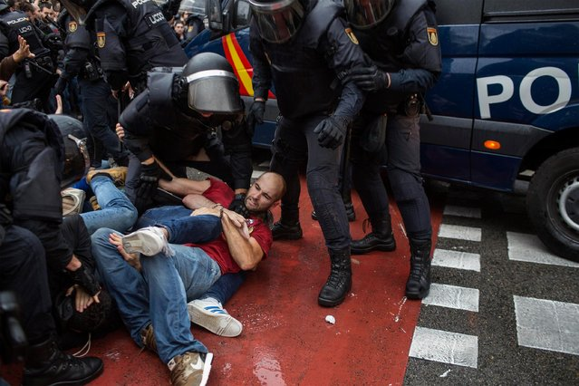 People clash with Spanish police officers outside the Ramon Llull polling station in Barcelona October 1, 2017 during a referendum on independence for Catalonia banned by Madrid. Spanish riot police fired rubber bullets and forced their way into activist- held polling stations in Catalonia on Sunday as thousands flooded the streets to vote in an independence referendum banned by Madrid. (Photo by Fabio Bucciarelli/AFP Photo)