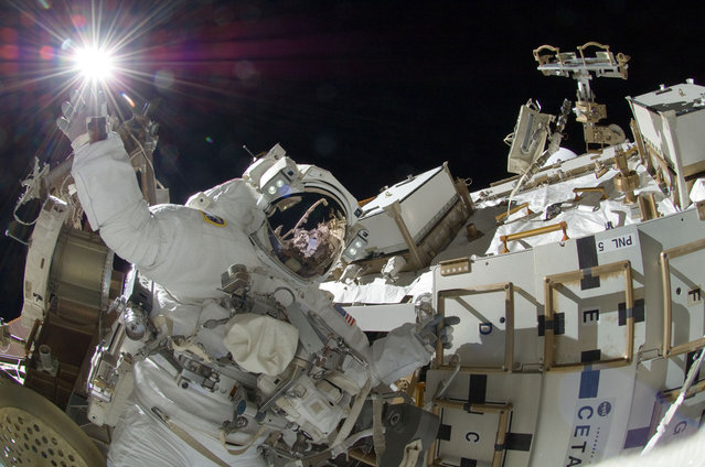 Above the Earth, NASA astronaut Sunita Williams, Expedition 32 flight engineer, appears to touch the bright sun during the mission's third session of extravehicular activity (EVA) on September 5, 2012. During the six-hour, 28-minute spacewalk, Williams and Japan Aerospace Exploration Agency astronaut Aki Hoshide (visible in the reflections of Williams' helmet visor), flight engineer, completed the installation of a Main Bus Switching Unit (MBSU) that was hampered by a possible misalignment and damaged threads where a bolt must be placed. They also installed a camera on the International Space Station's robotic arm, Canadarm2. (Photo by NASA)