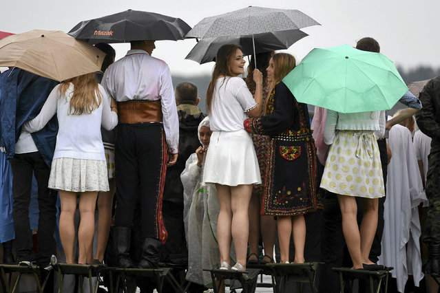 People sit atop chairs as they watch Pope Francis' departure at Balice airport near Krakow, Poland July 31, 2016. (Photo by Michal Lepecki/Reuters/Agencja Gazeta)