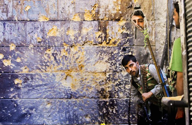 A Free Syrian Army soldier looks through a mirror which helps him see Syrian troops from the other side, as he takes his position with his comrade during fighting, at the old city of Aleppo city, Syria, on September 24, 2012. (Photo by Hussein Malla/Associated Press)