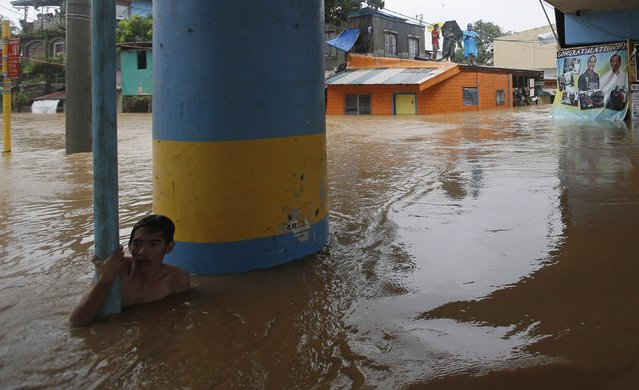 A man waits to be rescued during heavy flooding in Marikina, metro Manila, September 19, 2014. (Photo by Erik De Castro/Reuters)
