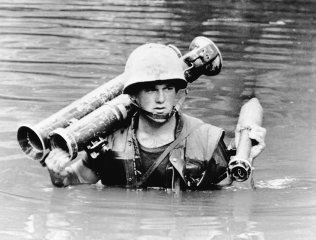 A U.S. marine carries a 3.5 inch rocket launcher and ammunition through a monsoon swollen creek in South Vietnam, October 14, 1966. The 2nd battalion of the 5th marines was patrolling the Jungle Mountains south of the demilitarized zone. (Photo by AP Photo/Merron)
