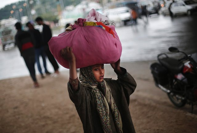 A girl displaced by heavy floods carries her belongings as she arrives at a free medical camp in Srinagar September 14, 2014. About 150,000 people were still stranded in their homes a week after Indian Kashmir's worst flood in over a century and fears grew on Sunday of an outbreak of diseases from vast fields of stagnant brown water. (Photo by Adnan Abidi/Reuters)