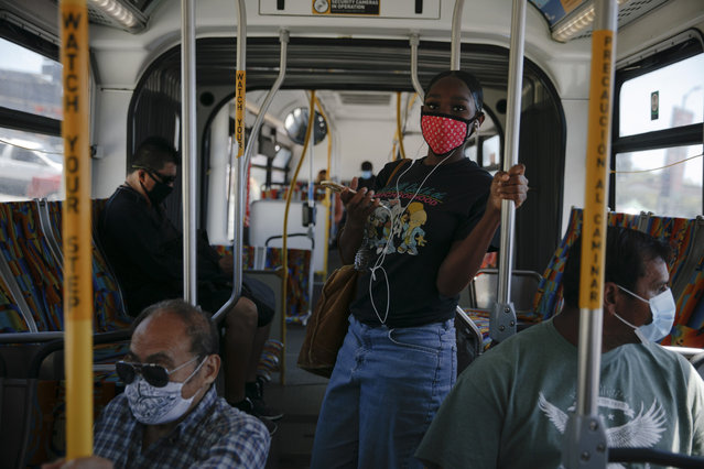 Commuters wearing masks ride a bus during the coronavirus pandemic in the Vermont Square neighborhood of Los Angeles, Thursday, May 21, 2020. While most of California took another step forward to partly reopen in time for Memorial Day weekend, Los Angeles County didn't join the party because the number of coronavirus cases has grown at a pace that leaves it unable to meet even the new, relaxed state standards for allowing additional businesses and recreational activities. (Photo by Jae C. Hong/AP Photo)
